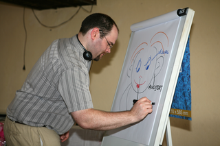 Male Midas trainer drawing on a flip board